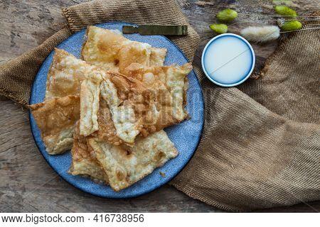 Homemade Sweet Crispy Thai Roti (thai Pancake) Served With Sweetened Condensed Milk On Ceramic Plate