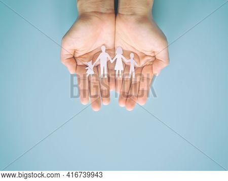 Hand Holding Family Paper Cut On Blue Background. Family Day Concept, Foster Care, Domestic Violence