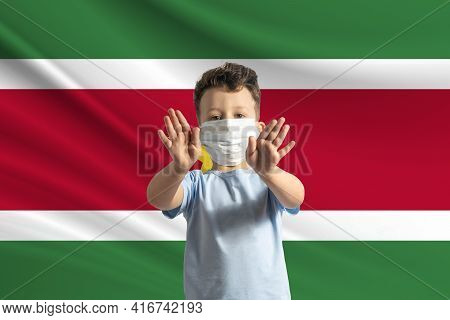 Little White Boy In A Protective Mask On The Background Of The Flag Of Suriname. Makes A Stop Sign W