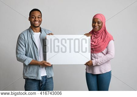 Cheerful Black Couple Holding Empty Placard For Advertisement