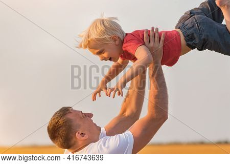 Dad And Child Playing With Son Together Outdoors. Father Throws Up Child.