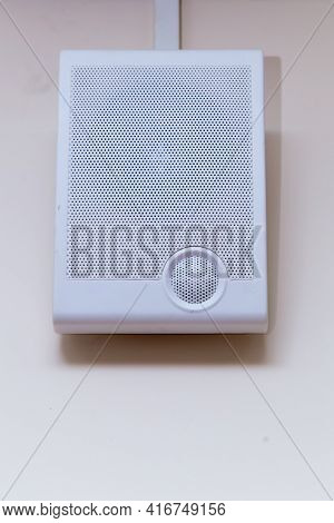 A White Radio Transmitter Hangs On A Beige Wall. On The Front Side There Is A Grill With Small Holes