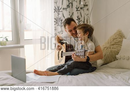 Father And Son Learn To Play The Acoustic Guitar In An Online Lesson. Happy Father's Day