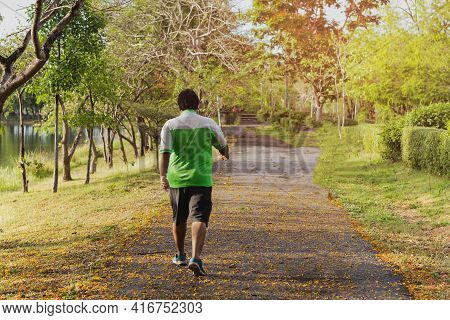 Asian Oversize Man Walking Exercise In The Park.