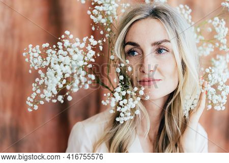 Close-up Portrait Of Charming Happy Woman In Spring Mood With Gypsophila Flowers On Her Head. Lifest