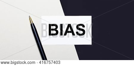 On A Black And White Background Lies A Pen And A White Card With The Text Bias