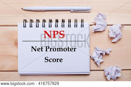 On A Wooden Background, A White Notebook With The Inscription Nps Net Promoter Score, A White Pen An