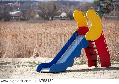 Childrens Slide Located In A Deserted Place. Dried Grass Field. Empty Playground. Sunny