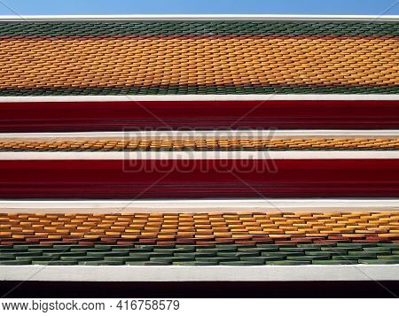 three layered roof, colorful clay tiles fish scales or repeated wave pattern with red wooden eaves of thai temple or ancient grand palace with blue sky, Asian art traditional exterior architecture