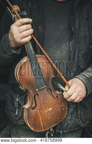 Old Violin In The Hands Of A Homeless Master