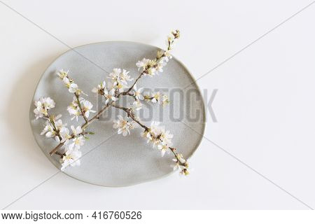 Closeup Flowering Branch Of Almond , Earthenware Plate And White Table Background. Floral Compositio