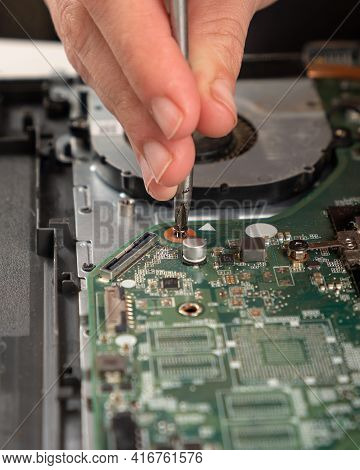 Laptop Maintenance, The Master Of The Service Center Unscrews The Motherboard With A Screwdriver .