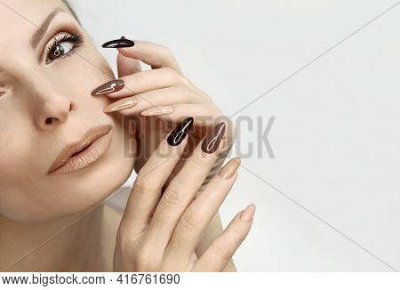 Brown And Beige Make Up And Manicure On The Long Shape Of The Nails Of A Woman.