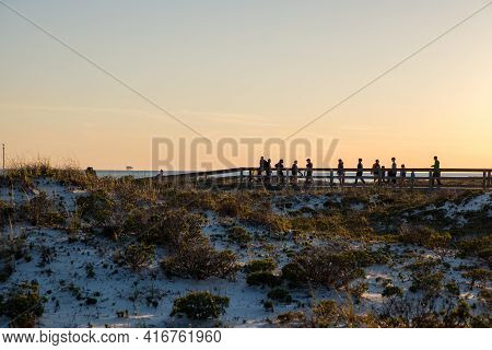 Gulf Shores, Al - April 2: Silhouetted People Walk On The Boardwalk Of The Beach At Sunset On April