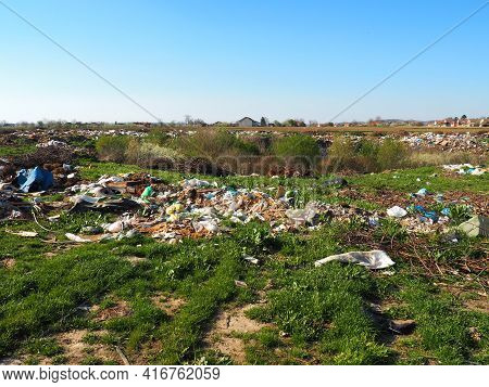 Garbage Dump Near The Village. Chaotic Unofficial Dump. Plastic, Bags, Paper, Glass, Biological Wast