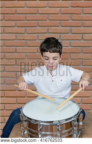 7 Year Old Kid Playing The Drums And Making A Funny Face. Brick Wall Background.