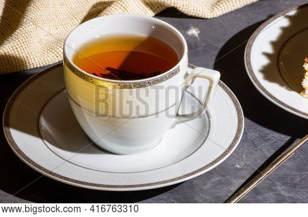 Cup Of Hot Black Tea On A White Saucer And A Linen Napkin, Black Background, Hard Light, Photo In A
