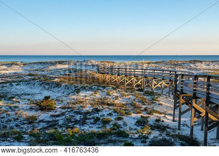 Late Afternoon On The Gulf Of Mexico With A Boardwalk, Sand Dunes And Gulf Waters As The Sun Begins