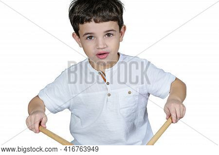 Close Up Of 7 Year Old Child Staring At The Camera And Playing The Drums. White Background.