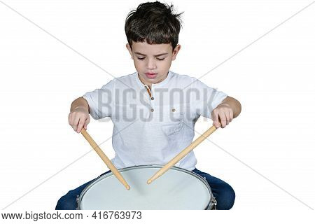 7 Year Old Child Focused On His First Drum Lessons. White Background.
