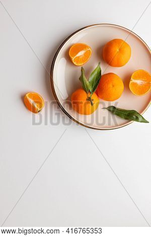 Fresh Tangerine Or Clementin Fruits On A Beige Plate With Gold Rim On A White Background. Colorful F