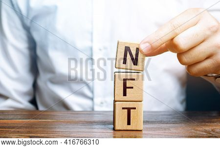 Man Puts Together Word Nft From Blocks. Nft Non-fungible Token. Selling Digital Art Assets Through I