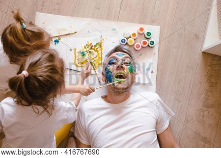 Happy Dad Is Lying On The Floor, The Children Paint His Face With Watercolors. Father's Day. Happy D