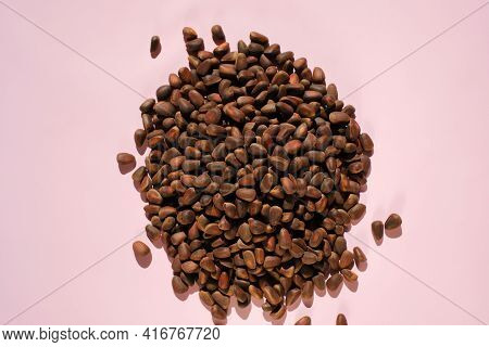 Pine Nuts Heap On A Pink Background. Nuts And Seeds. Cedar Nuts. Organic And Healthy Superfood.