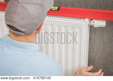 Caucasian Heating And Cooling Technician Installing Heating Radiator Using His Spirit Level Tool.