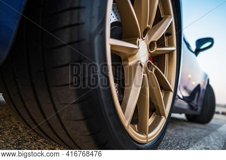 Performance Vehicle Sporty Car Golden Alloy Wheels Ground Level Point Of View.