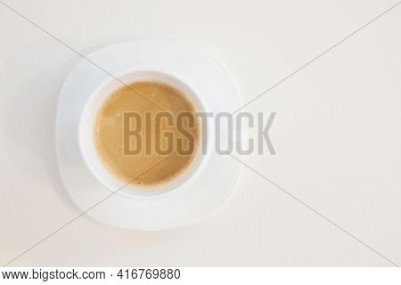 Close up top view of a white cup of coffee on soucer isolated on white background with copy space on left side