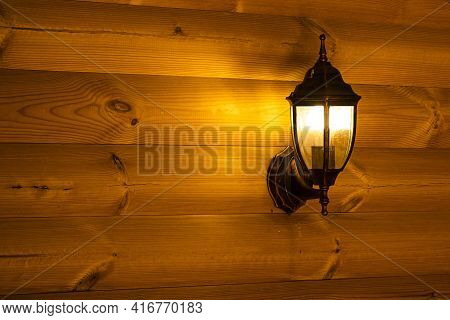 The Wall Mounted Electric Street Light On The Wall Of A Wooden Log House Shines Yellow In The Evenin