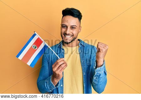 Young arab man holding costa rica flag screaming proud, celebrating victory and success very excited with raised arm