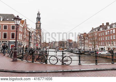 Amsterdam, Netherlands - February 24, 2017: Bicycles Stand Parked On The Bridge In Old Town Of Amste