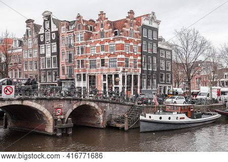 Amsterdam, Netherlands - February 25, 2017: Street View Of Amsterdam Old Town With People Walking Th