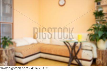 Blurred Backdrop Of Trendy Minimal Home Interior With Large Corner Sofa, Houseplants, Creative Woode