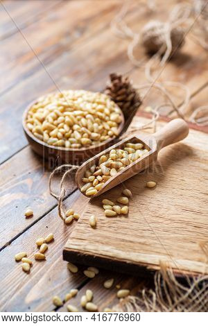 Still Life Of Pine Nuts In A Bowl, A Scoop With Nuts On A Wooden Cutting Board On The Table, A Rope