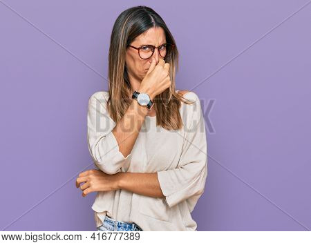 Young woman wearing casual clothes and glasses smelling something stinky and disgusting, intolerable smell, holding breath with fingers on nose. bad smell