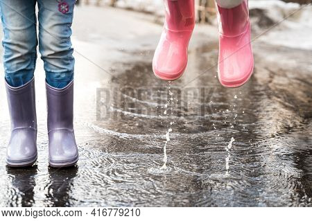 Little Girls In Pink, Purple Waterproof Rubber Boots Cheerfully Jumps Through Puddles On Street Road