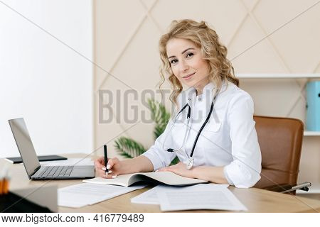 Medicine And Health Care Concept. Woman Doctor In White Uniform Working In Personal Cabinet, Sitting