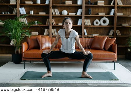 Young African American Woman Stretching Legs, Doing Fitness Training On Yoga Mat At Home. Adult Fema