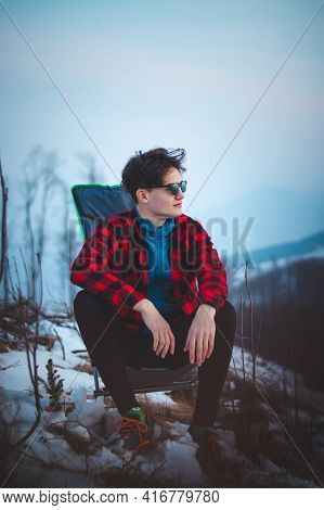 Handsome Teenager Aged 15-20 In A Plaid Red-black Shirt And Sunglasses On A Chair By The Tent. Watch