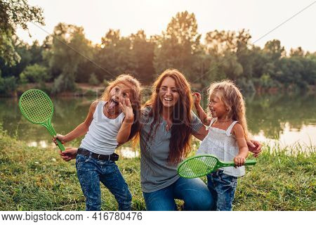 Mother's Day. Family Having Fun After Playing Badminton By Summer River. Mother Laughing And Grimaci