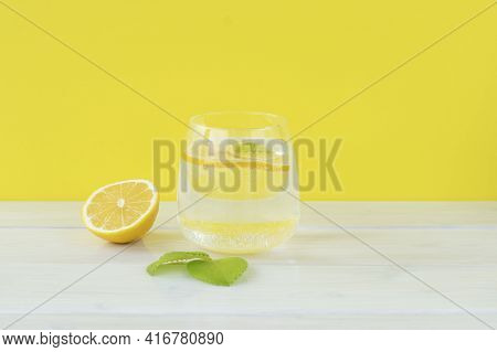 Transparent Glass Of Water, Round Lemon Slice And Mint Leaf On Bright Yellow Trendy Background. Deto
