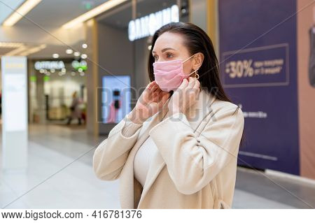 A Woman Puts On A Medical Protective Mask In A Public Place