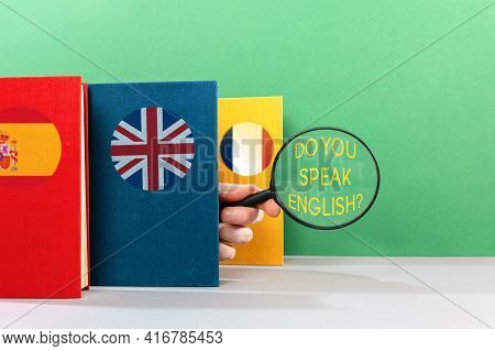A Male's Hand Peeks Out From Behind An English Textbook And Holds A Magnifying Glass. Text Do You Sp