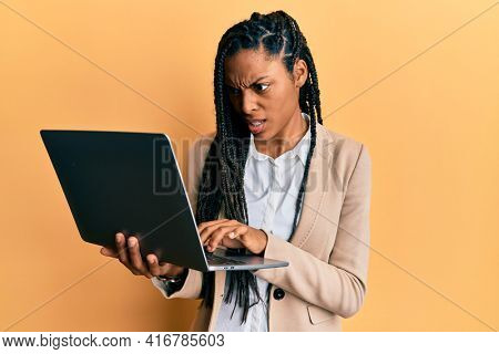 African american woman working using computer laptop angry and mad screaming frustrated and furious, shouting with anger. rage and aggressive concept.