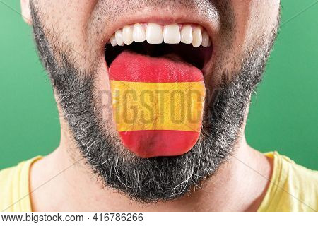 Native Speaker. The Protruding Tongue Of A Bearded Man Is Close-up, In The Colors Of The Spanish Fla