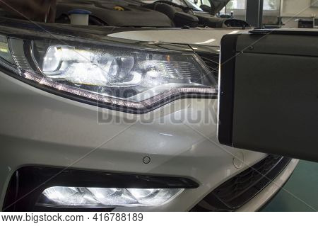 Checking The Direction Of The Light Of The Right Headlight Of A White Car With The Help Of A Device
