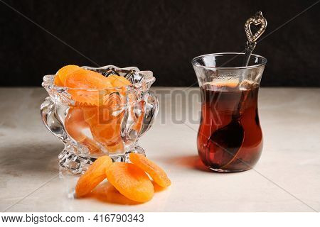 Turkish Tea In Traditional Turkish Glass And Dried Apricots In Glass Vase. Traditional Snack During